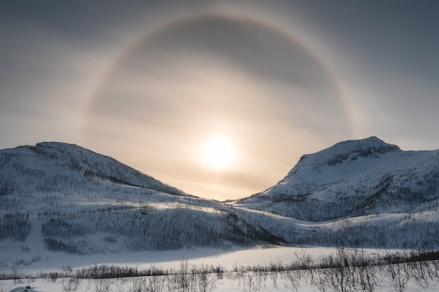 Śnieżne pasmo górskie z aureolą słoneczną w zimie o poranku