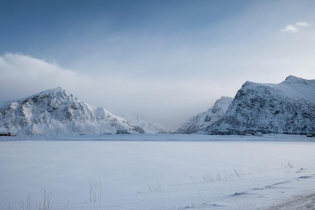 Śnieżne pasmo górskie z zachmurzonym niebem w zimie na plaży skagsanden