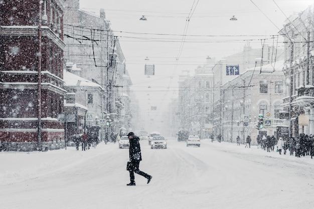 Śnieżne piękne ruchliwe miasto z samochodami i przechodniem, obfite opady śniegu. sparaliżowane miasto podczas złych warunków zimowych