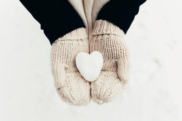 Śnieżne serce śnieżka w rękach rękawiczek dziewczyny. niewyraźne tło. wysokiej jakości zdjęcie