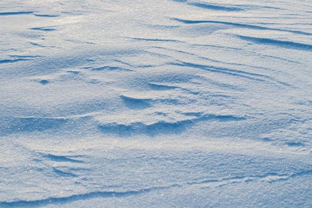 Śnieżne tło, pokryta śniegiem powierzchnia ziemi po porannej zamieci w słońcu z wyraźnymi warstwami śniegu