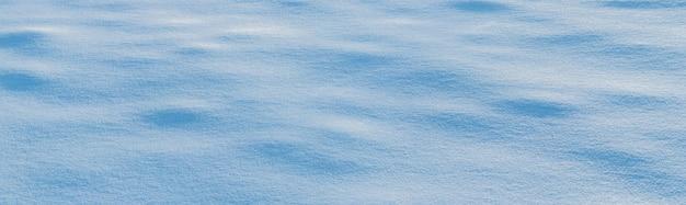 Śnieżne tło, śnieżna powierzchnia z wyraźnie wyrażoną teksturą śniegu w porannym słońcu