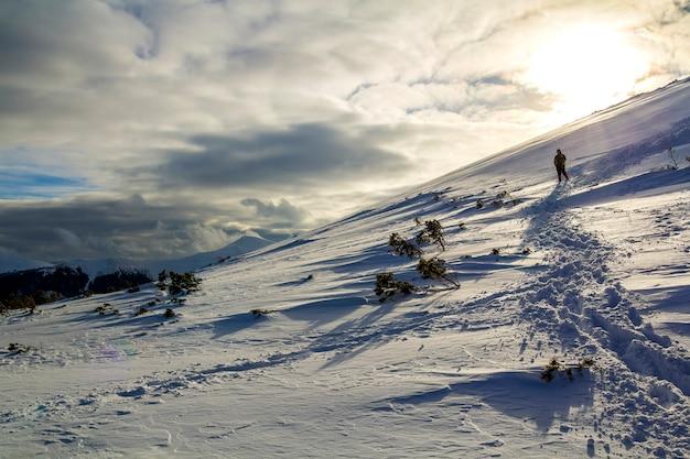 Śnieżne wzgórze z odciskami stóp i daleki turysta wędrujący z plecakiem w górach