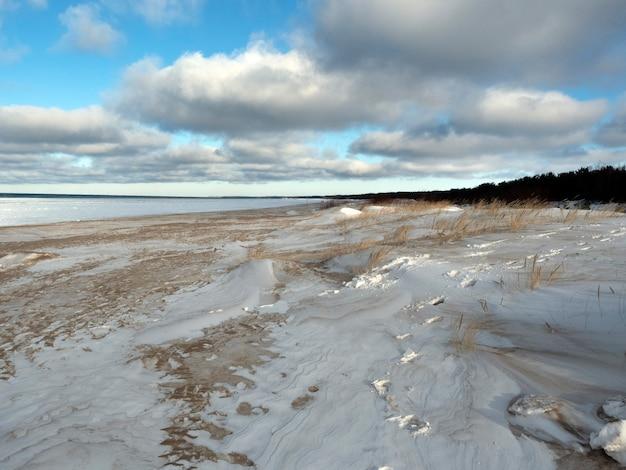 Śnieżny brzeg zamarzniętego morza. jasne niebo z wyrazistymi chmurami.