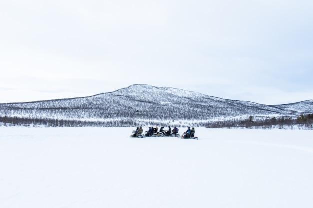 Śnieżny dzień z ludźmi jadącymi na skuterach śnieżnych w oddali na północy szwecji