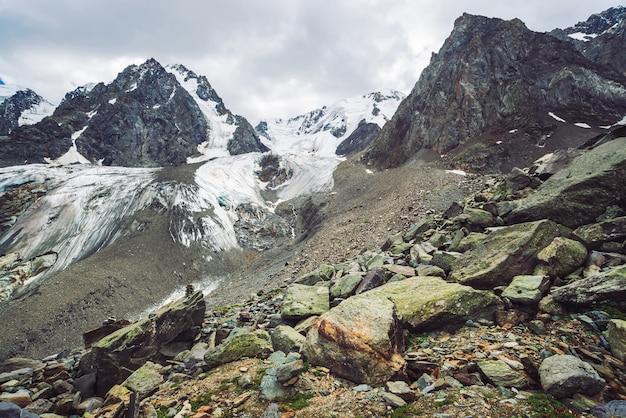 Śnieżny gigantyczny pasmo górskie pod chmurnym niebem. skalista grań ze śniegiem. ogromny lodowiec. lodowaty stok ze strumieniami wody. cudowne góry. atmosferyczny minimalistyczny górzysty krajobraz przyroda.
