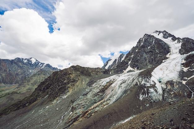 Śnieżny gigantyczny pasmo górskie pod chmurnym niebem. skalista grań ze śniegiem. ogromny lodowiec. lodowaty stok ze strumieniami wody. cudowne góry. atmosferyczny minimalistyczny górzysty krajobraz przyrody.