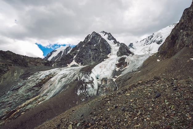 Śnieżny gigantyczny pasmo górskie pod chmurnym niebem.