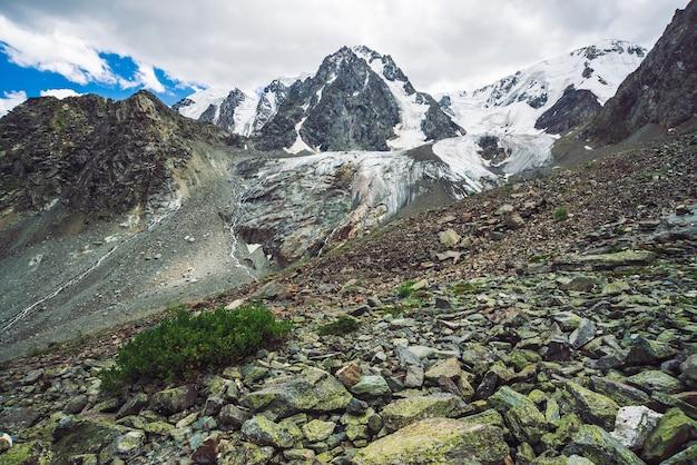 Śnieżny gigantyczny pasmo górskie pod zachmurzonym niebieskim niebem