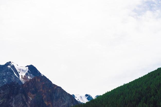 Śnieżny góra wierzchołek za wzgórzem z lasem pod chmurnym niebem.
