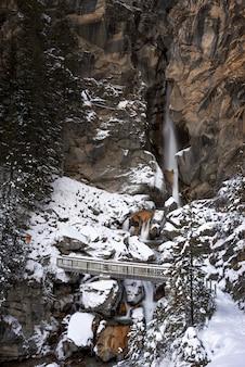Śnieżny krajobraz z mostem i wodospadem