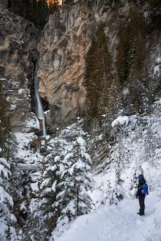 Śnieżny krajobraz z osobą patrząc na wodospad