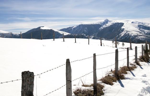 Śnieżny krajobraz z płotem na pierwszym planie i górami w tle.