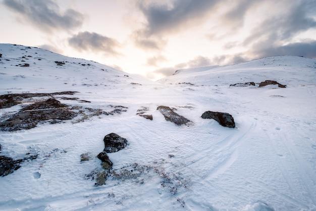 Śnieżny krajobraz z światłem słonecznym w dolinie