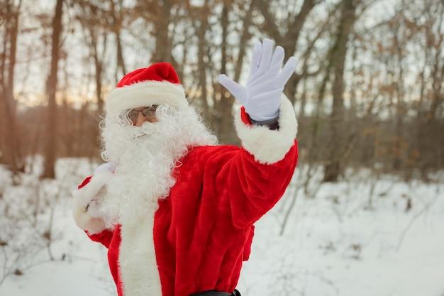 Śnieżny mikołaj idący ulicą niesie ze sobą dużą torbę prezentów