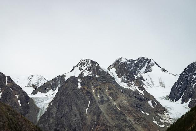 Śnieżny szczyt góry w błękitne jasne niebo. skalisty grzbiet pod chmurami w słoneczny dzień. nastrojowy minimalistyczny krajobraz majestatycznej przyrody.