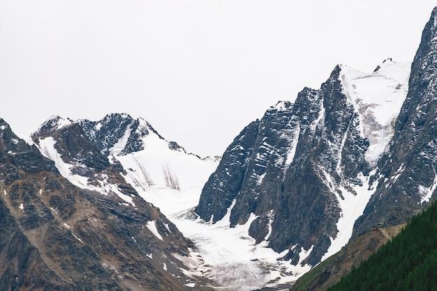 Śnieżny szczyt góry za wzgórzem z lasem pod pochmurnym niebem. skalisty grzbiet przy pochmurnej pogodzie.