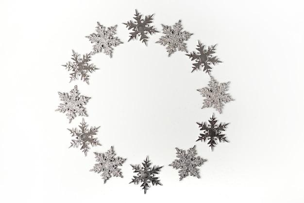 Śnieżynka koło rama świąteczna dekoracja na białej ścianie