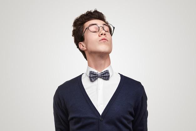 Snobistyczny młody mężczyzna w okularach zamykający oczy i podnoszący głowę na szarym tle