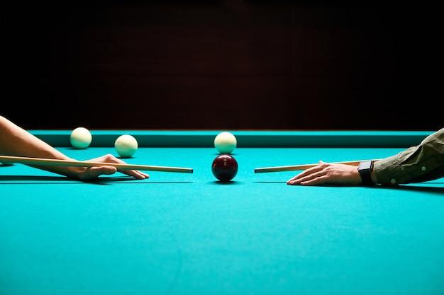 Snooker - zbliżenie dwóch mężczyzn grających w bilard, celujących w piłkę na stole bilardowym
