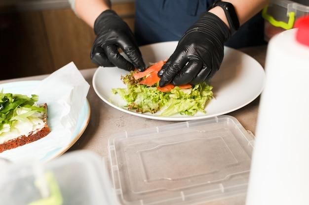 Snop robi sałatki warzywnej z wędzonym łososiem w restauracji.