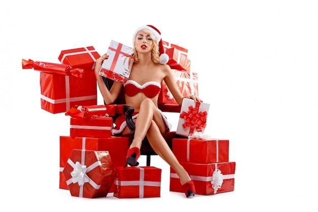 Snow maiden siedzi w pobliżu prezentów, trzymając prezent, uśmiechając się.