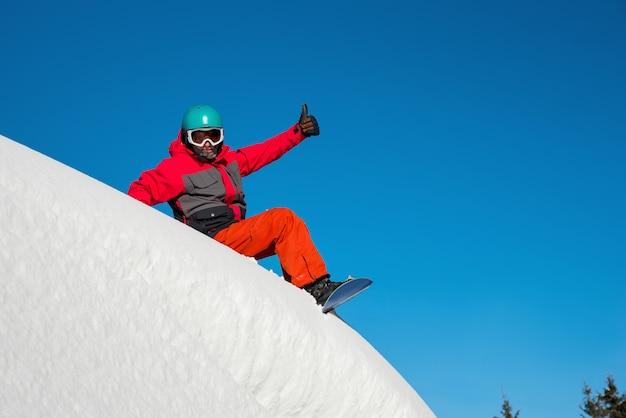 Snowboarder odpoczywa na górze góry