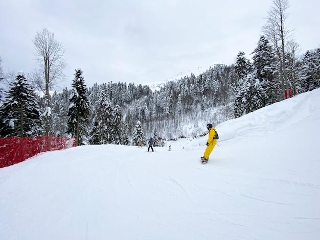 Snowboarder w żółtym kombinezonie snowboardowym