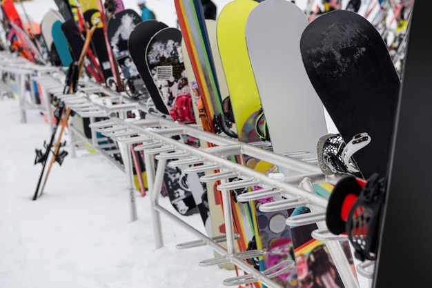 Snowboardy i narty trzymane razem