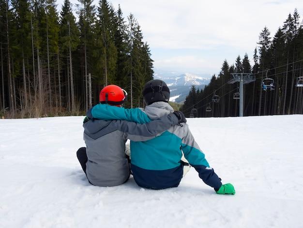 Snowboardziści chłopaki siedzą na śniegu i odpoczywają po nartach