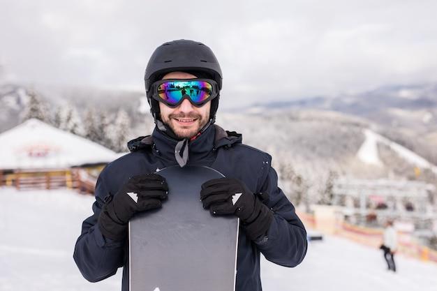 Snowboardzista człowiek stoi ze snowboardem. portret zbliżenie.
