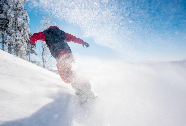 Snowboardzista jedzie na stoku w słoneczny zimowy dzień w górach.