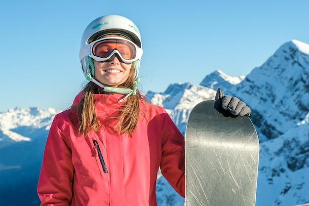 Snowboardzista kobieta stojąca z snowboard. zbliżenie portret wesoły snowboardzista na szczycie stoku narciarskiego
