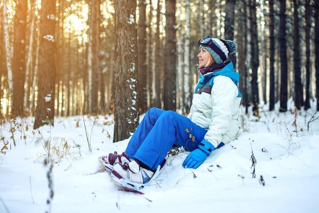 Snowboardzista kobieta z snowboard jest odpoczynku, siedząc na śniegu