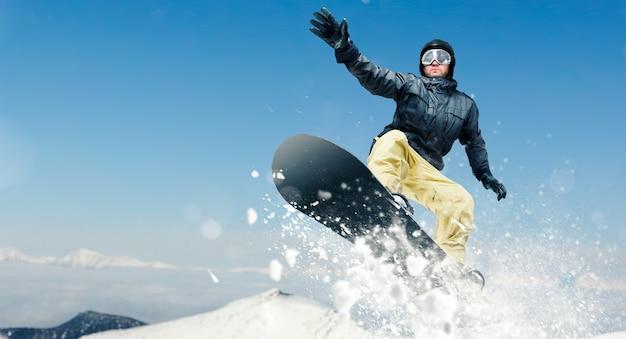 Snowboardzista mężczyzna, niebezpieczny zjazd w akcji