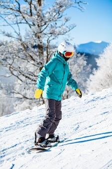 Snowboardzista na łyżwach w górach z głębokim błękitnym niebem