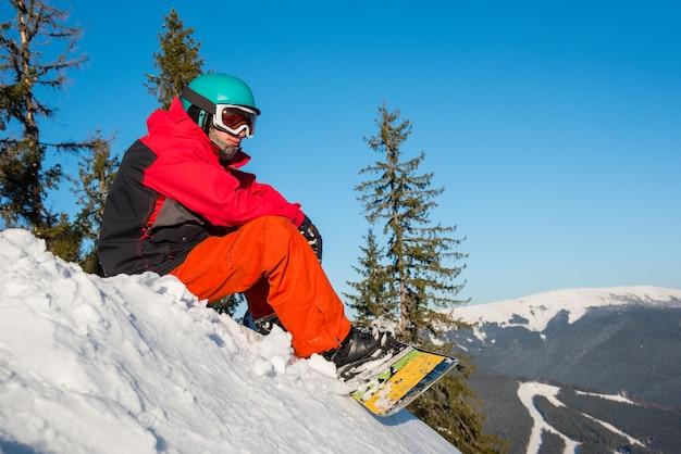 Snowboardzista na szczycie stoku w zimowy wieczór