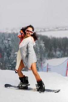 Snowboardzista sexy kobieta w stroju kąpielowym, sporty zimowe, pani w bikini.