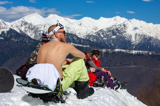 Snowboardzista siedzi topless na zaśnieżonym szczycie góry i opala się.