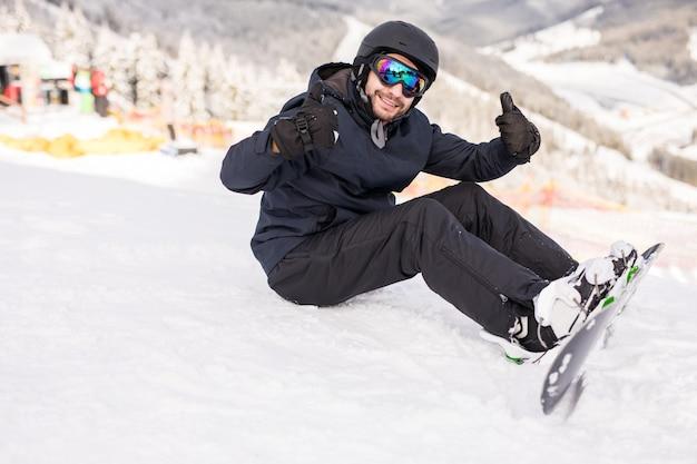 Snowboardzista siedzi wysoko w górach na skraju stoku i przed jazdą patrzy w kamerę