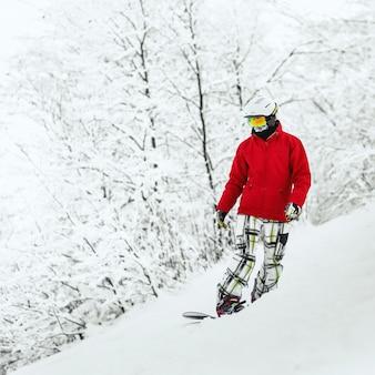Snowboardzista stoi na wzgórzu otoczonym lasem