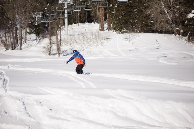 Snowboardzista sylwetka w ośrodku narciarskim, jazda na nartach w górach