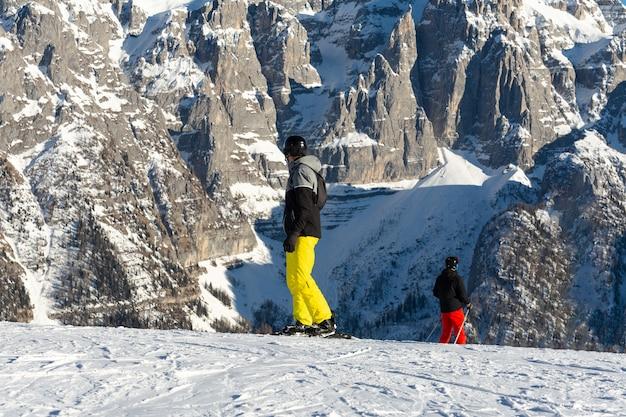 Snowboardzista w czarnej kurtce i żółtych spodniach stoi na stoku narciarskim na tle góry.