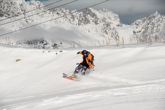 Snowboardzista w kolorowej odzieży sportowej na śnieżnym wzgórzu