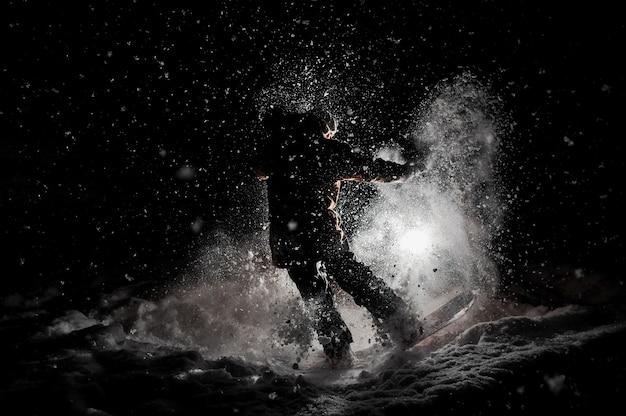 Snowboardzista w odzieży sportowej skoki na pokładzie w nocy
