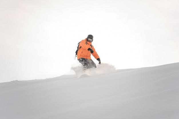 Snowboardzista w pomarańczowej odzieży sportowej jedzie w dół stoku góry na białym niebie