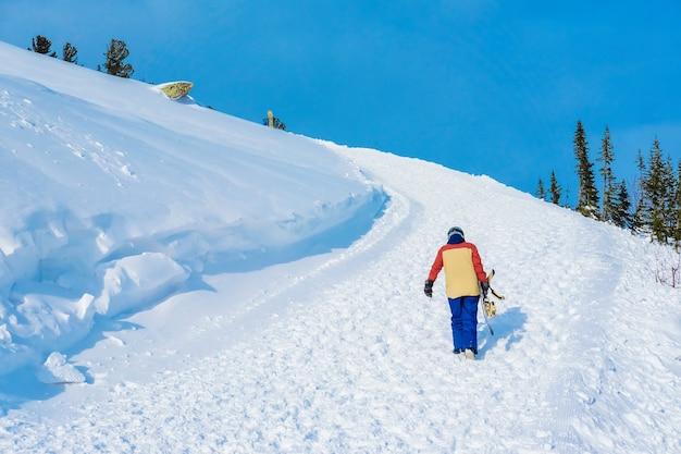 Snowboardzista wspina się po drodze na szczycie góry. snowboardzista na tle jasnego nieba.