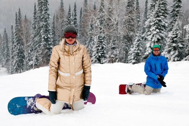 Snowboardzistka dziewczyna w złotej odzieży sportowej i strój w lesie ośnieżonych wysokich gór. koncepcja wypoczynku apres ski
