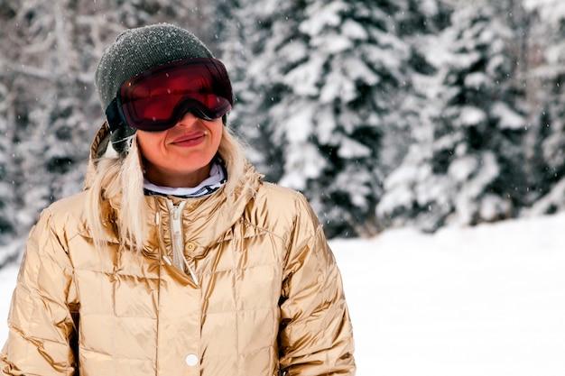 Snowboardzistka w złotej odzieży sportowej i stroju stoi w lesie ośnieżonych wysokich gór. koncepcja wypoczynku apres ski