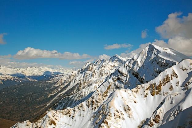 Snowy górskie szczyty przeciw błękitne niebo